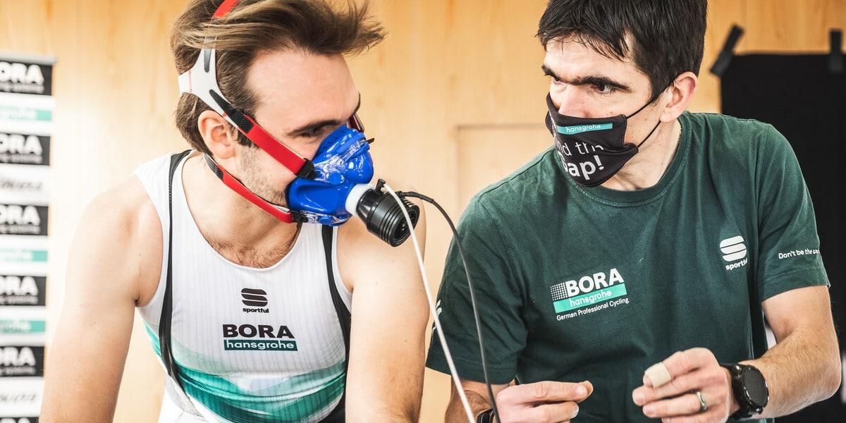 Sportler mit Maske wird von Trainer bei einem medizinischen Check auf Leistung überprüft