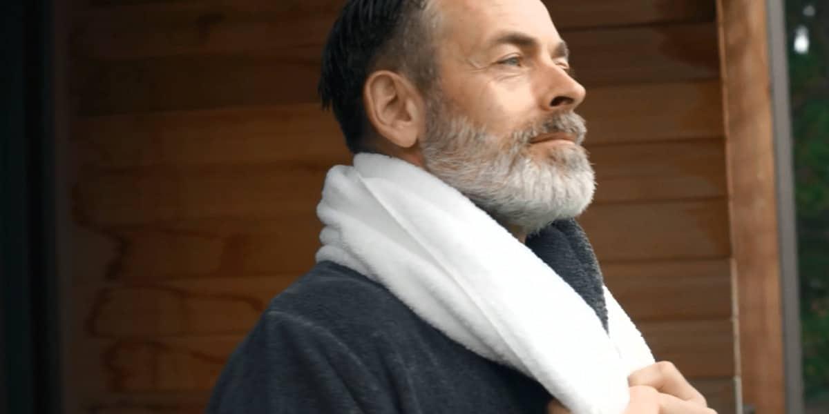 Mann mit Bademantel und Handtuch über Hals