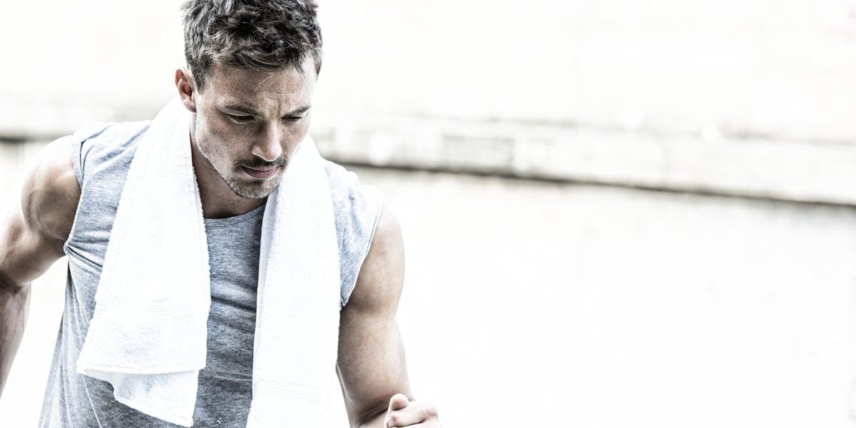 Mann beim Training mit Handtuch über Hals