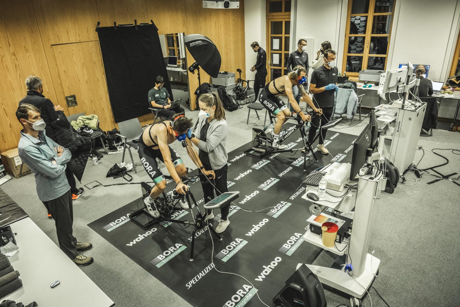 Testaufbau mit zwei Radfahrern an Ergometern trainierend mit überwachenden medizinischen Angestellten