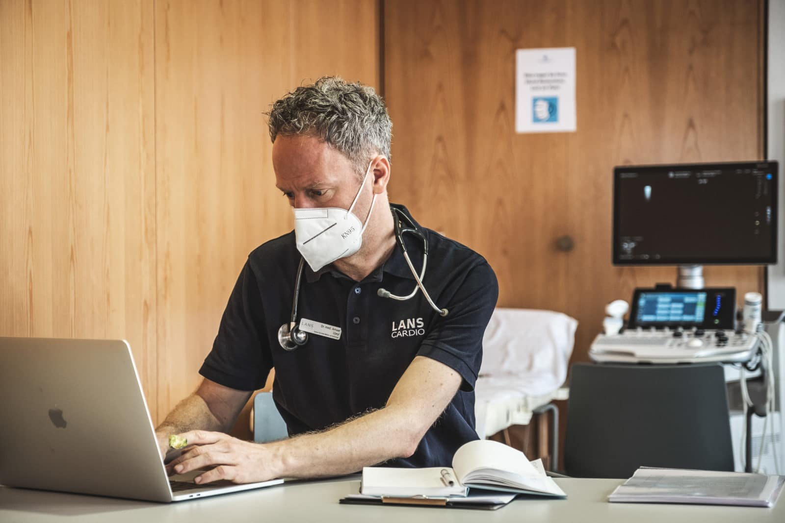 Am Schreibtisch sitzender Arzt tippt konzentriert am Laptop