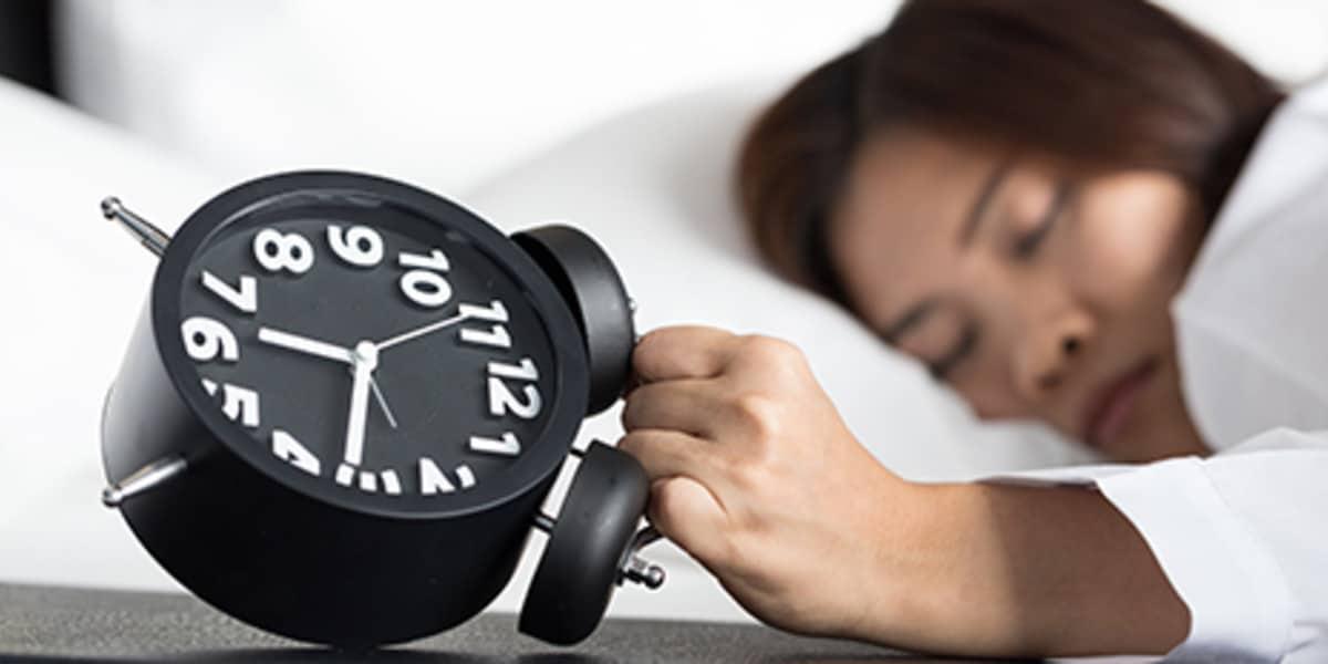 schlafende Frau und Wecker