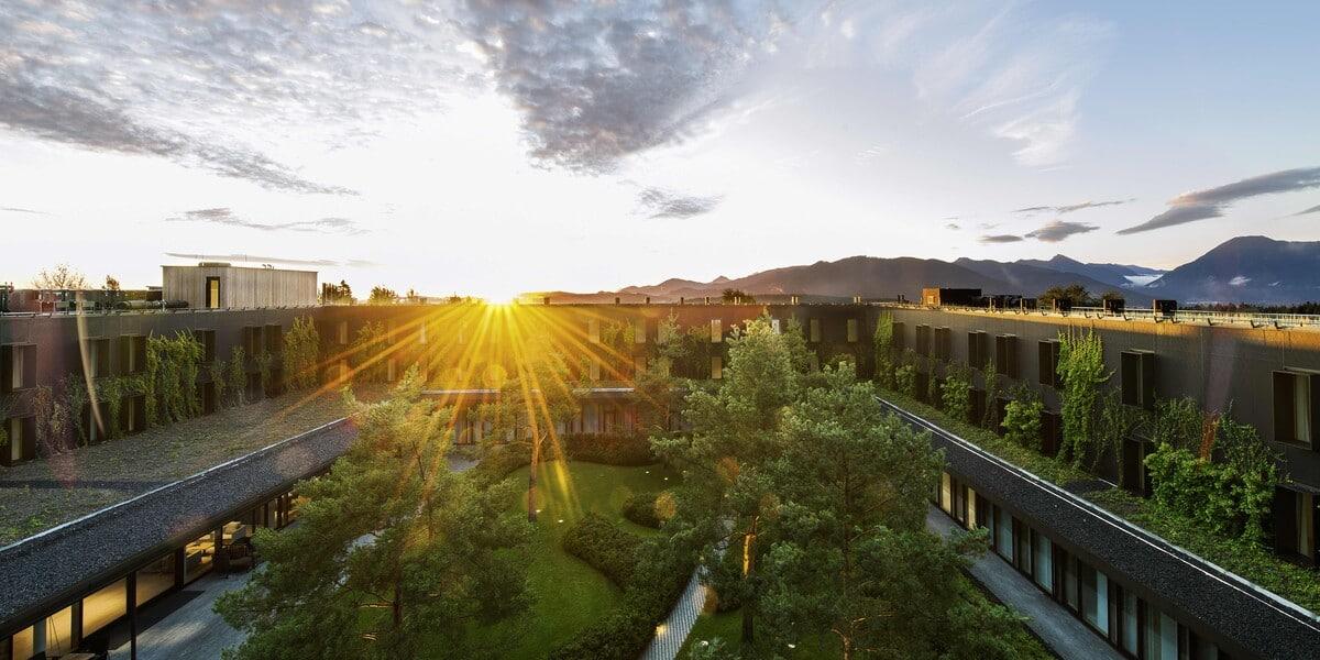 Sonnenaufgang über dem Dach des Resorts Lanserhof Tegernsee inmitten von Natur