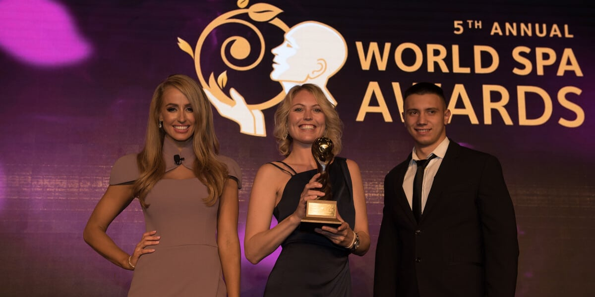 Drei Gewinner*Innen des World Spa Awards posieren auf Bühne mit Pokal für die Kamera