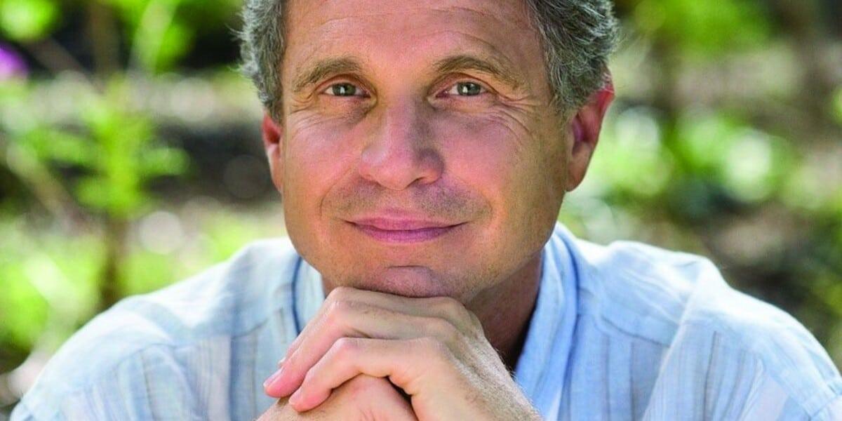 Portrait eines freundlich lächelnden Mannes umgeben von grüner Natur