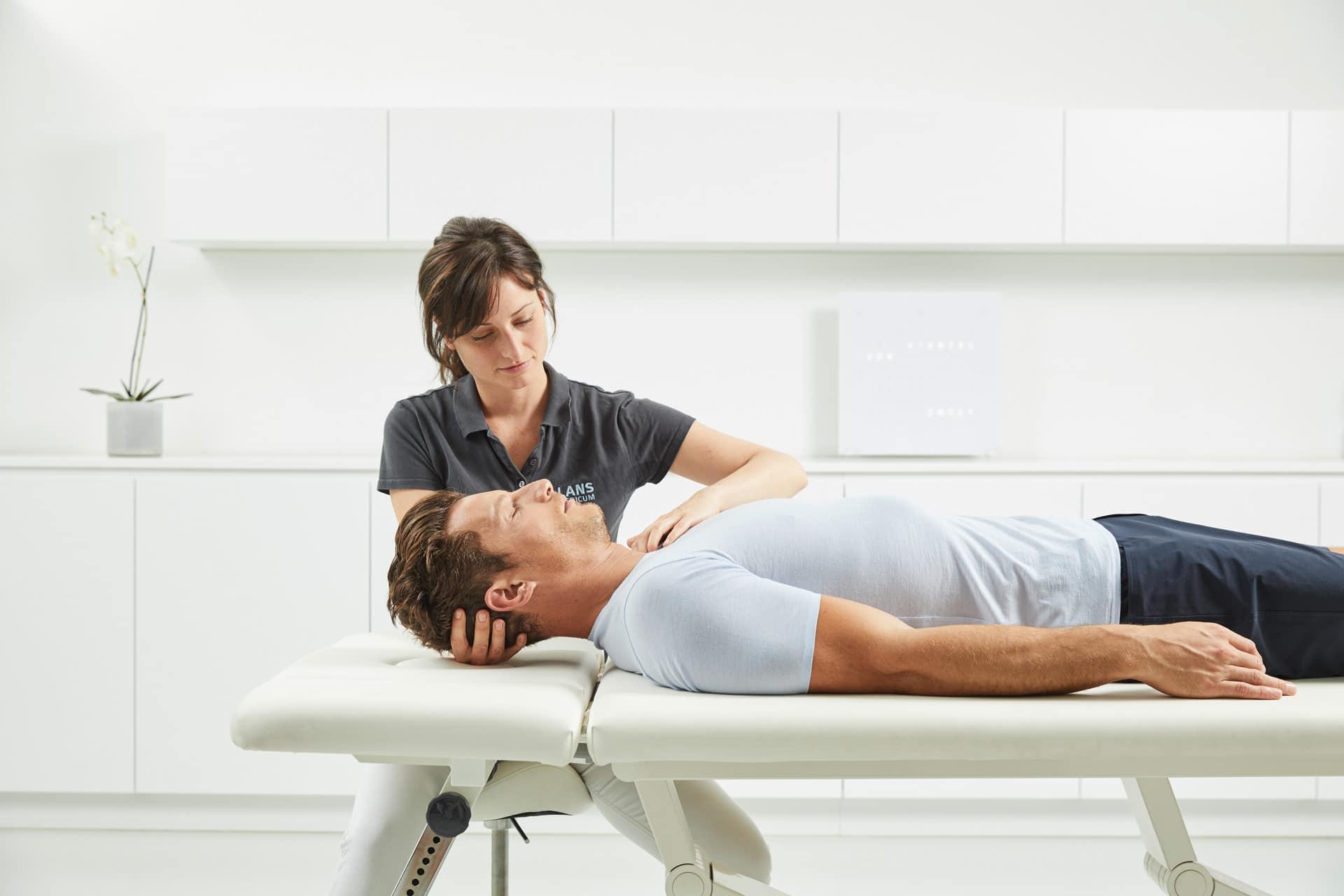 Therapeutin bei einer Kraniosakral-Behandlung mit Patienten