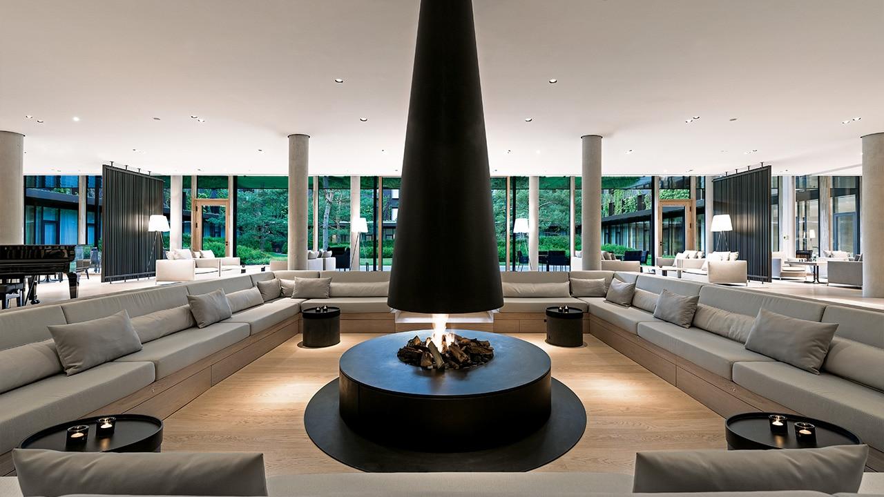 Innenansicht der Lounge im Lanserhof Resort Tegernsee mit Couchlandschaft und Feuerstelle