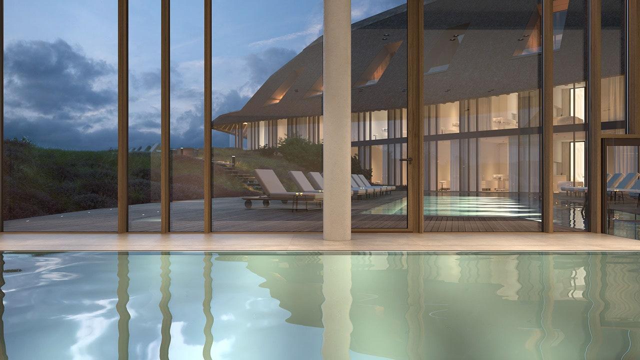 Blick nach draussen vom Indoorpool des Lanserhof Resorts Sylt bei Daemmerung